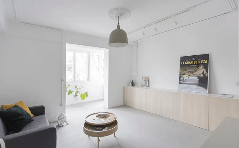 The living room is done with some simple furniture and a balcony fills the space with light