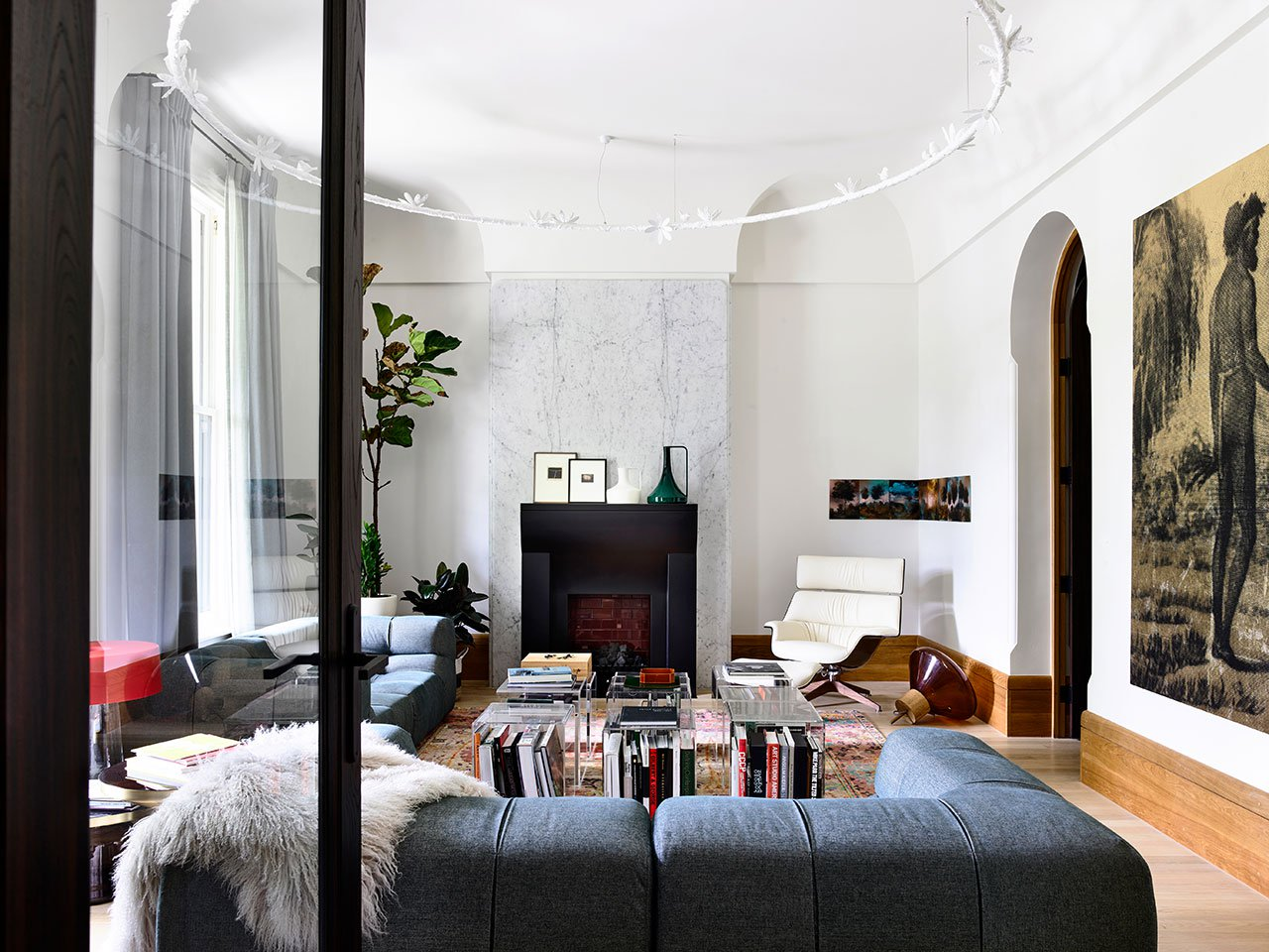 The living room shows off gorgeous art, stylish furniture, a unique hanging piece and a stylish faux fireplace