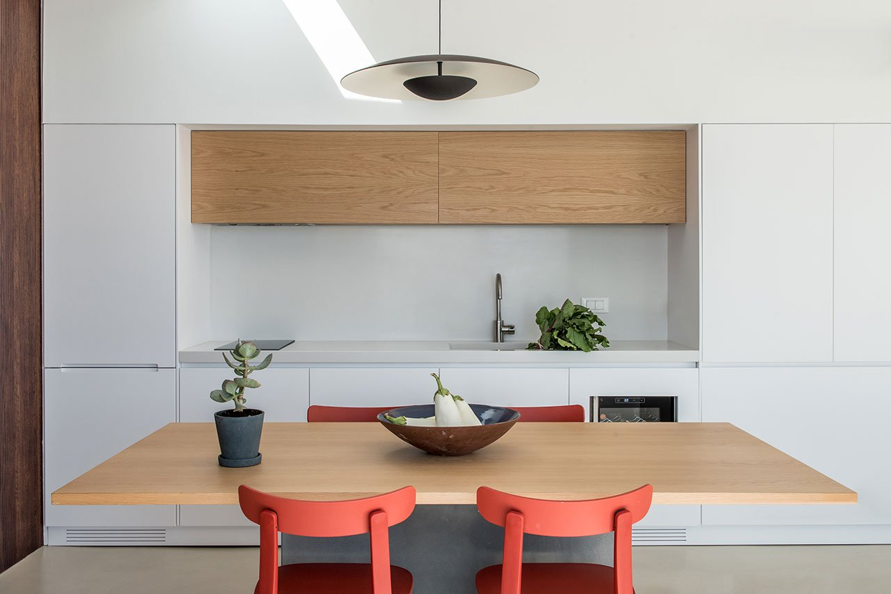 The minimalist kitchen with a dining zone in white and with touches of wood