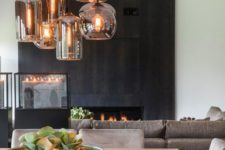 04 a fireplace clad with dark wooden panels makes up the coolest statement in this neutral space