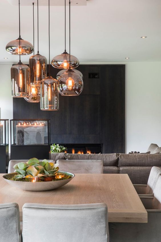 a fireplace clad with dark wooden panels makes up the coolest statement in this neutral space