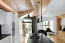 04 a minimalist white kitchen plus a sleek black kitchen island and a geometric ceiling for a wow effect