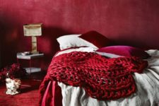 04 an all-red bedroom with a red wall, carpet, pillows and a chunky knit blanket for a passionate look