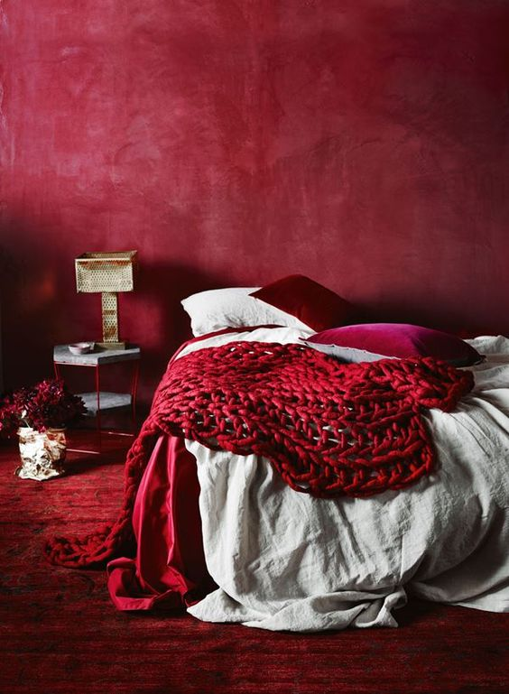 an all-red bedroom with a red wall, carpet, pillows and a chunky knit blanket for a passionate look