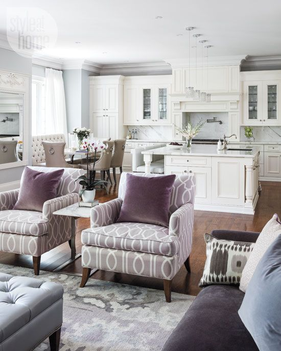 purple velvet chairs separate the living room and the kitchen and dining space
