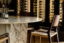 05 A small dining space features a marble table, woven chairs and a large lit up glass wine cooler