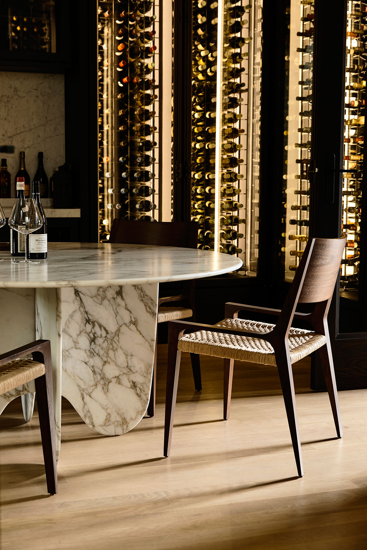 A small dining space features a marble table, woven chairs and a large lit up glass wine cooler
