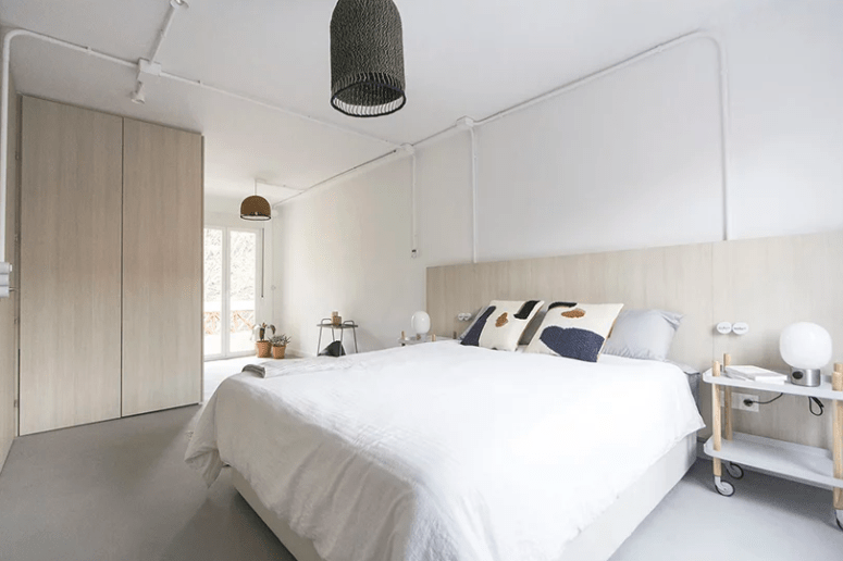 The bedroom includes a large bed, a couple of fun nightstands and a wicker lampshade