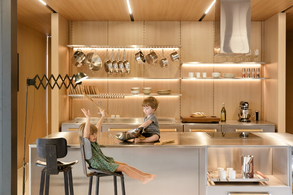 The kitchen shows off lit up shelves and metal surfaces, it looks ultra modern and shiny