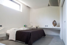 05 The master bedroom is done in white with acrhitectural geometric details, a metal bed and a floating desk or vanity