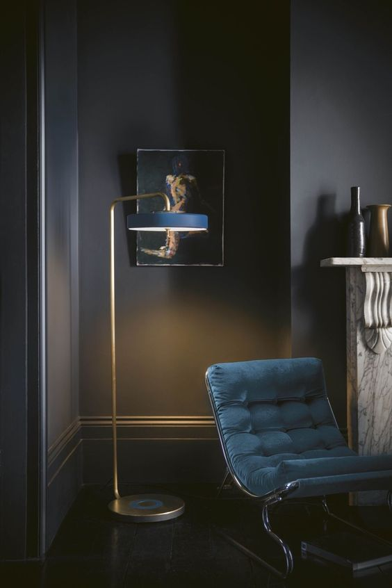 a chic floor lamp with aged copper and a narrow navy lampshade is a refined touch to your space