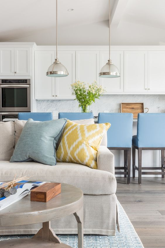 a large sofa marks the living space and the blue chairs show off the kitchen