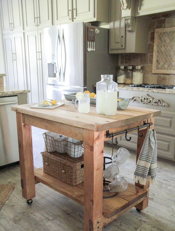 a rustic wooden kitchen island on casters with holders and hooks plus a storage space underneath