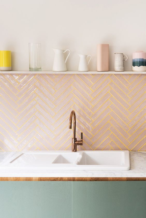 blush tiles clad in a chevron pattern and spruced up with sunny yellow grout for a modern backsplash