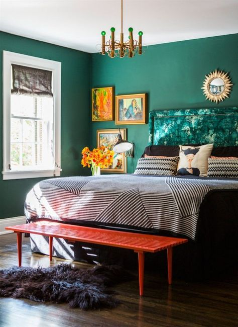 bold emerald walls make up a cool colorful space and artworks and furniture continue it
