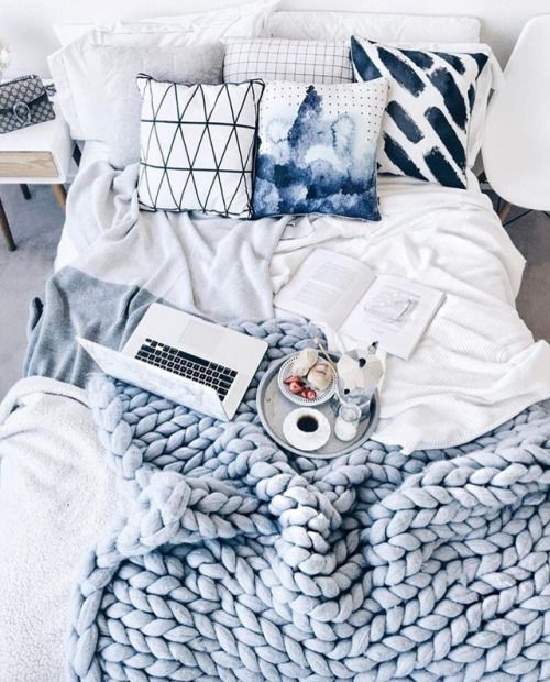 bright printed pillows and a matching powder blue chunky knit blanket for a welcoming bedroom