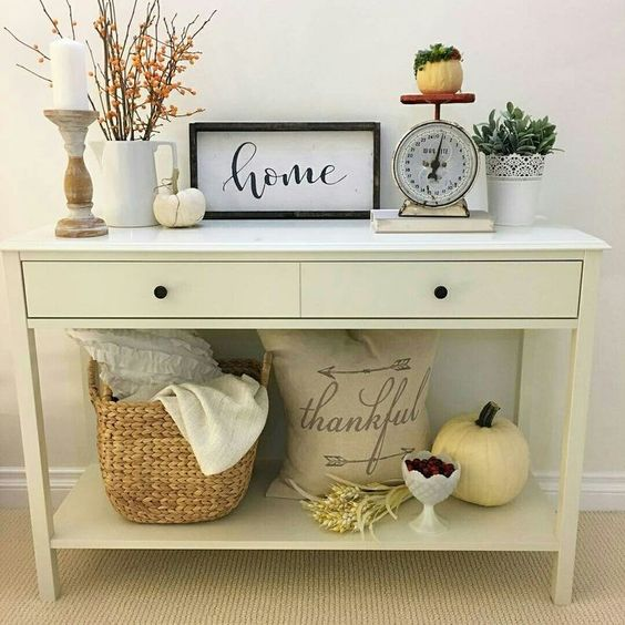 simple fall styling with a couple of pumpkins, berries, greenery and a basket with blankets