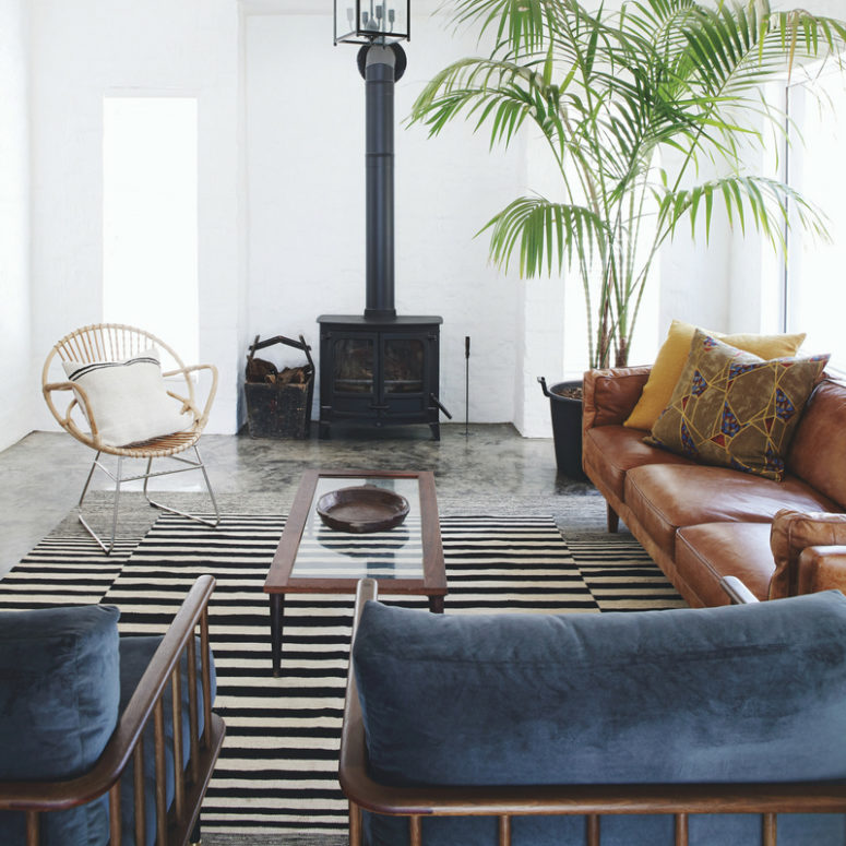 The living room features African aesthetics and modern comfy furniture, look at that vintage hearth