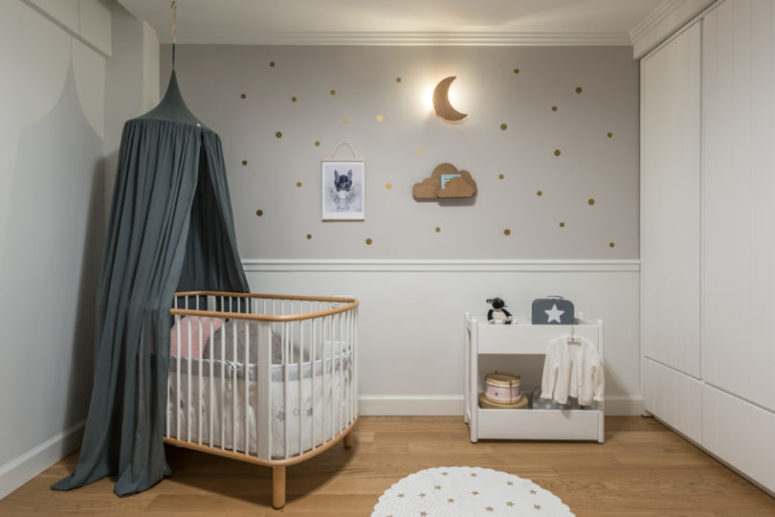 The nursery is a peaceful space done in neutrals, with little gold accents and a slate grey canopy for a touch of color
