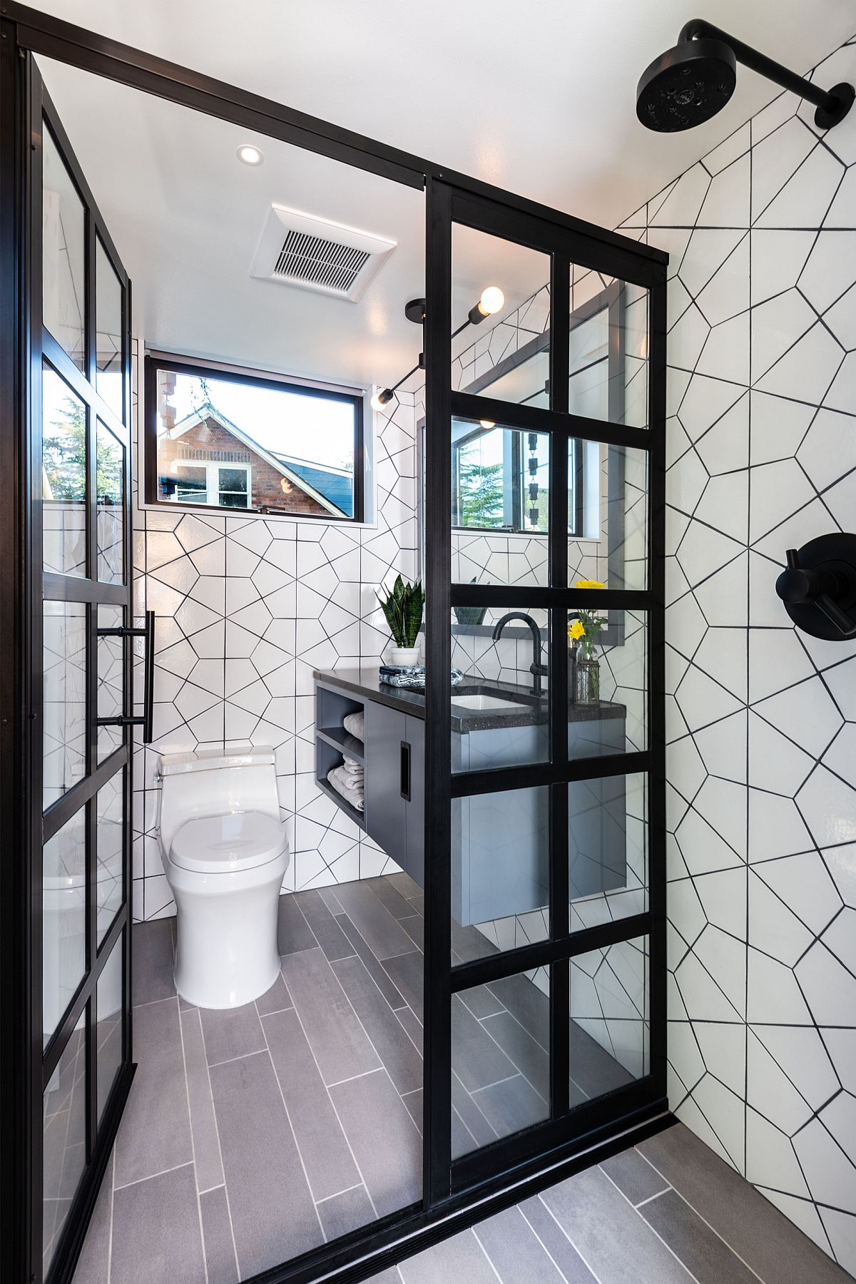 There's a small mudroom with white tiles, a floating vanity and small windows