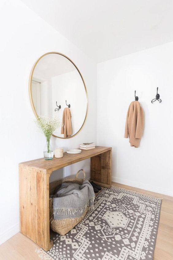 a console table on tall legs to use the space under it for storage is a smart idea for an entryway