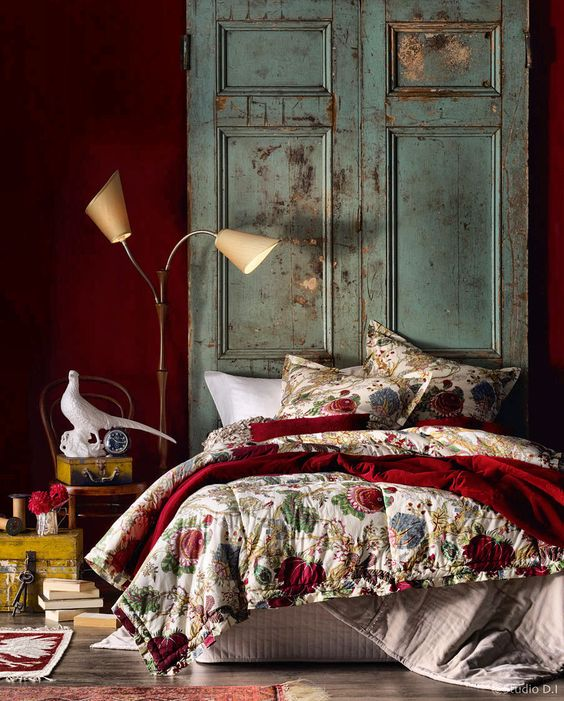 a deep red statement wall and a matching bedspread add color and interest to the room