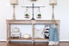 06 a fall farmhouse console table with white pumpkins, pillows and greenery in pots