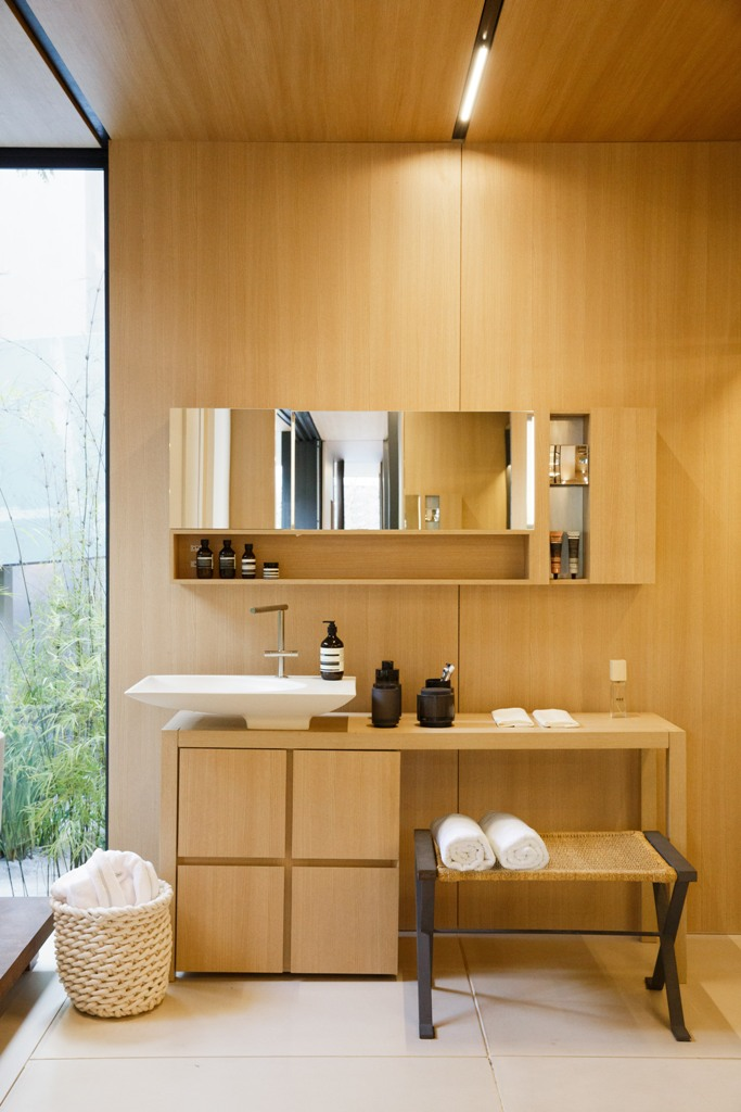 The bathroom features the same materials and comfy furniture with everything necessary