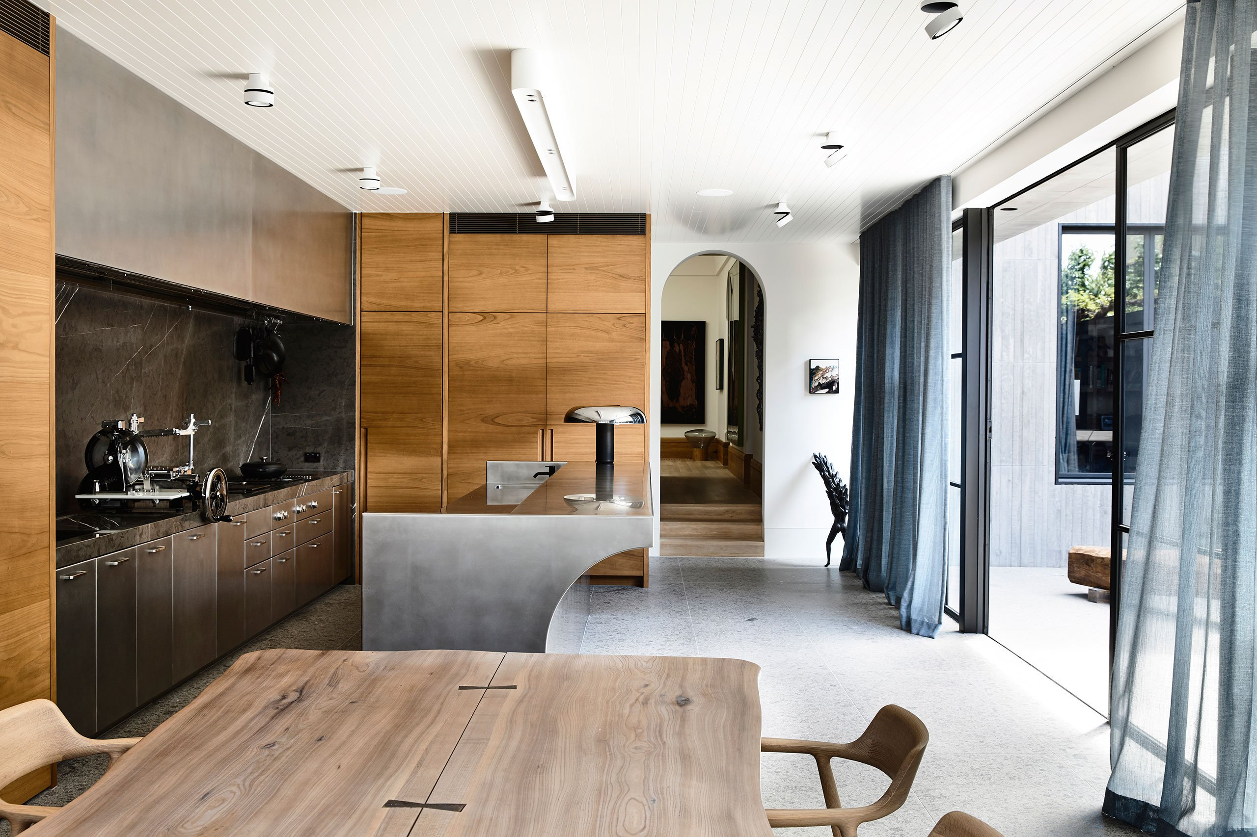 The kitchen is done with plywood and metal cabinets and a gorgeous metal kitchen island with curved lines, it may be opened to outdoors