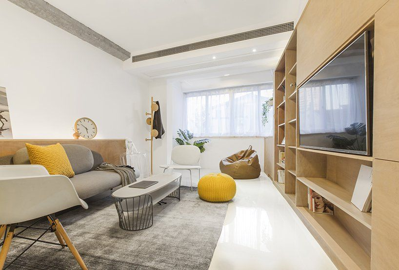 The living room is done in white, grey and yellow touches, there are exposed beams and pillars
