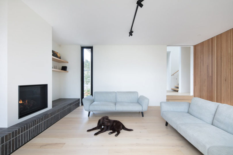 The living room is done with light grey sofas, a wood plank wall, a built in fireplace and some windows
