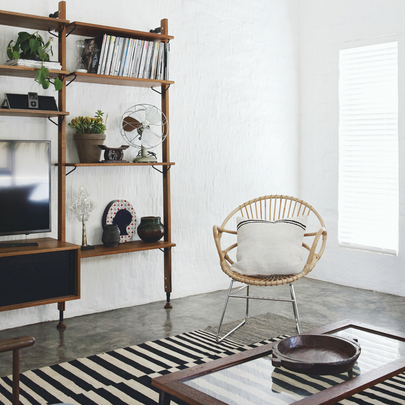 The shelving unit is an open one to keep the airy feeling on, and dark stained wood adds a contrasting touch