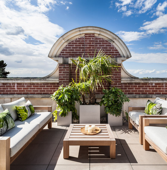 The terrace features a central sitting space with potted plants and contemporary furniture