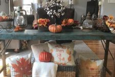 07 a bold fall console in teal with faux pumpkins, fall leaves, cotton and wire baskets with pillows