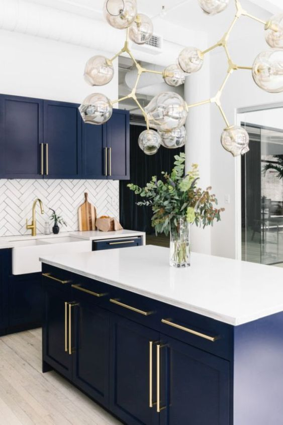 a chic kitchen in white, navy as a secondary color and gold for elegant touches