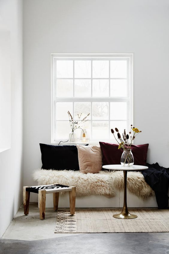 a cozy nook with a blush, plum and black velvet pillow, faux fur and a dried floral arrangement is a truly fall space