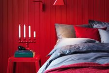 07 a red wooden plank wall, a matching sconce and a nigthstand create a super colorful space