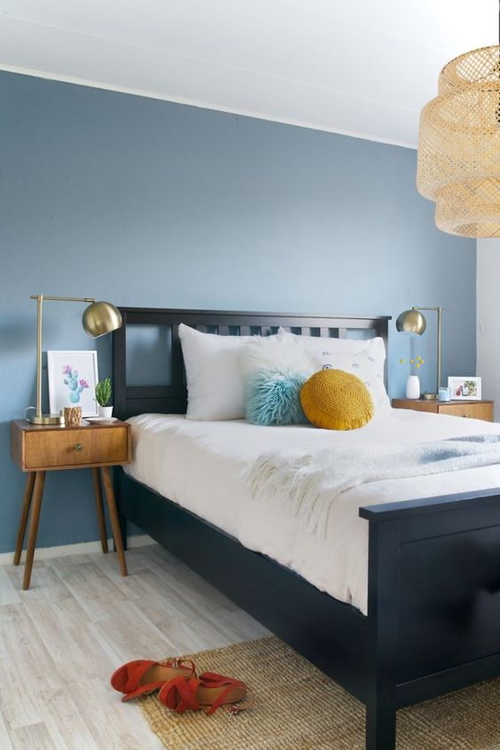 a slate blue accent wall and mustard touches add color to the mid century modern bedroom