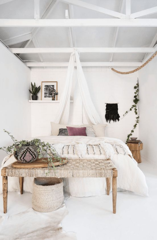 a woven bench, a basket and a woven planter, a fringe blanket and some greenery for a white boho space
