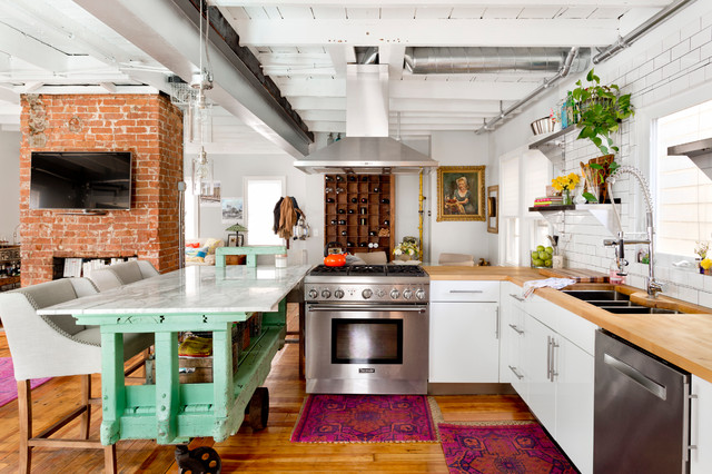 bold printed rugs, an aqua kitchen island and some potted greenery for a strong boho feel