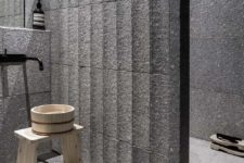 08 The bathroom is clad with stone tiles and reminds of Eastern spas