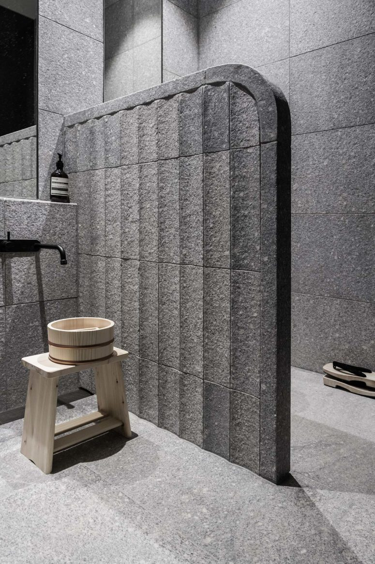The bathroom is clad with stone tiles and reminds of Eastern spas