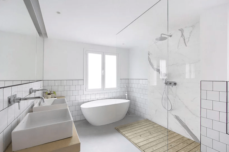 The bathroom is done with tow sinks, an oval bathtub and a minimalist shower done with marble and wood