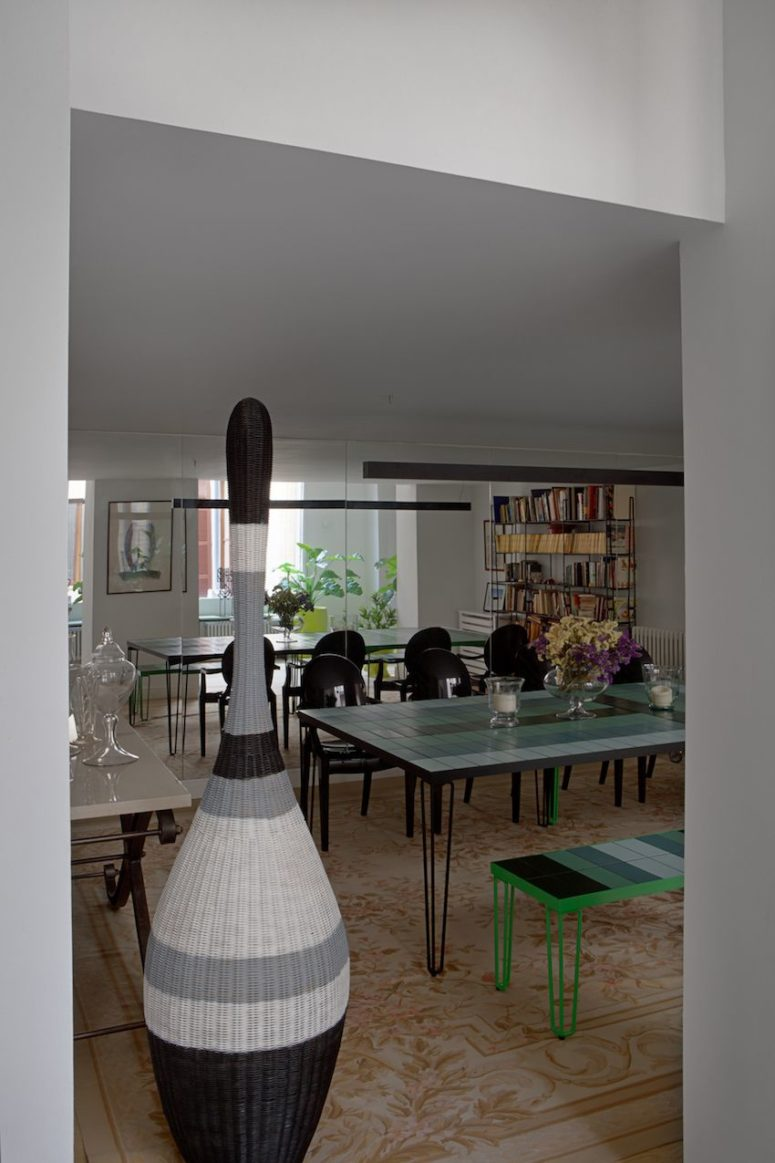 The dining room is done with modern colorful furniture and a mirror wall