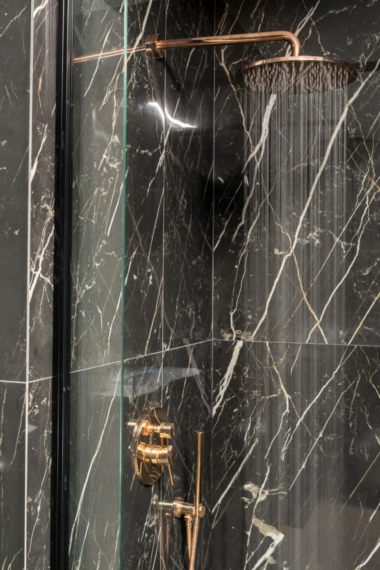 The master bathroom is clad with black marble tiles and is done with edgy copper fixtures
