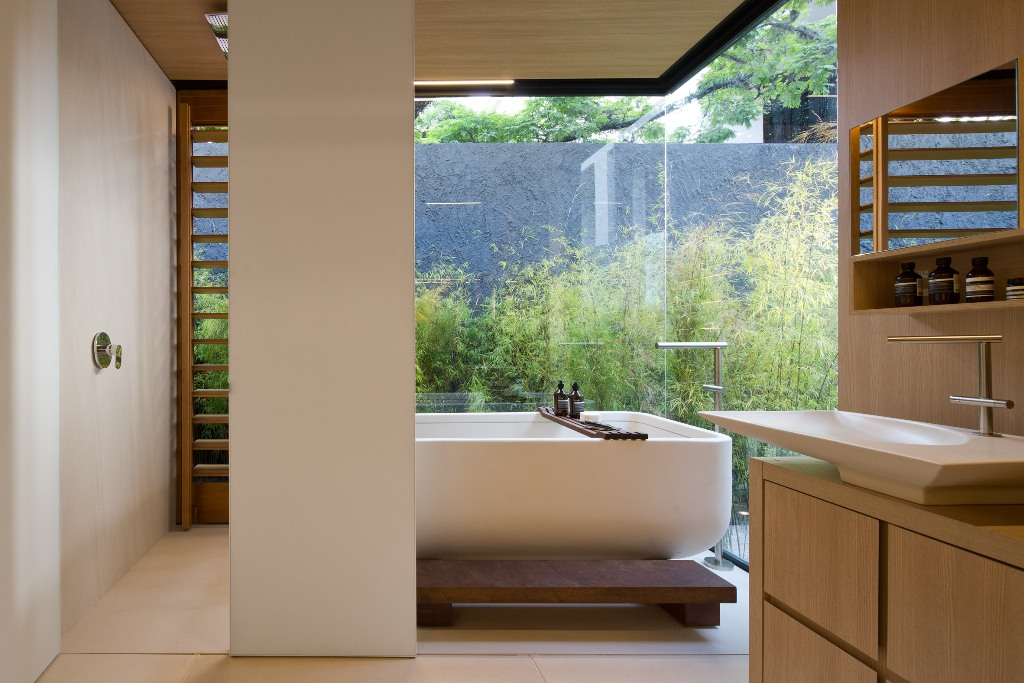 bathroom with large windows showing a courtyard