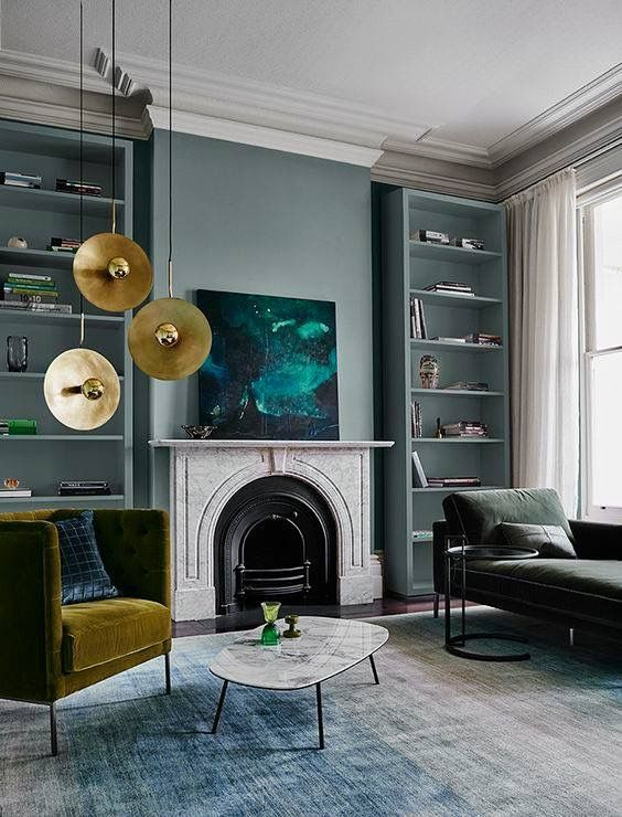 a bold emerald artwork and gilded pendant lamps over the mustard chair make the space fall like