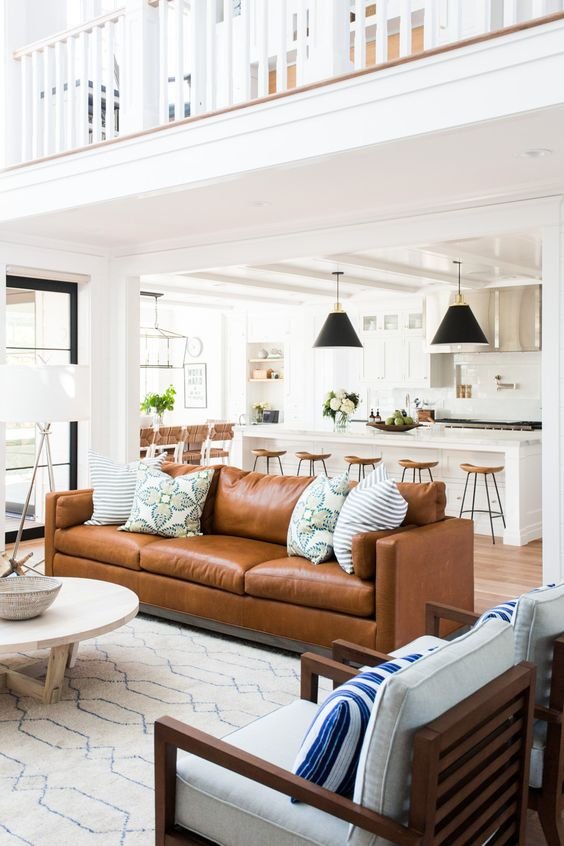 a brown leather couch as the main point on this large open layout, it makes statement with color