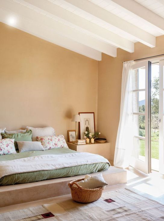 a chic bedroom with white as the main color, tan as a secondary and sage green for soft accenting