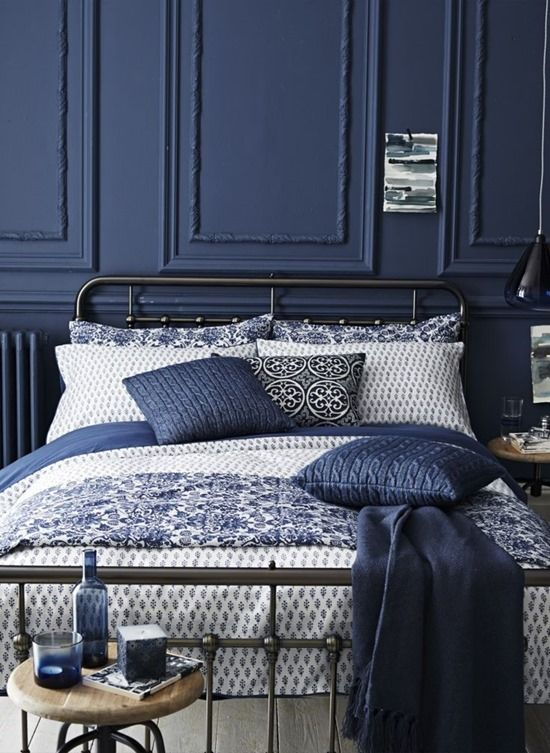 a dark blue wall with wainscoting and matching pillows for a relaxing moody space